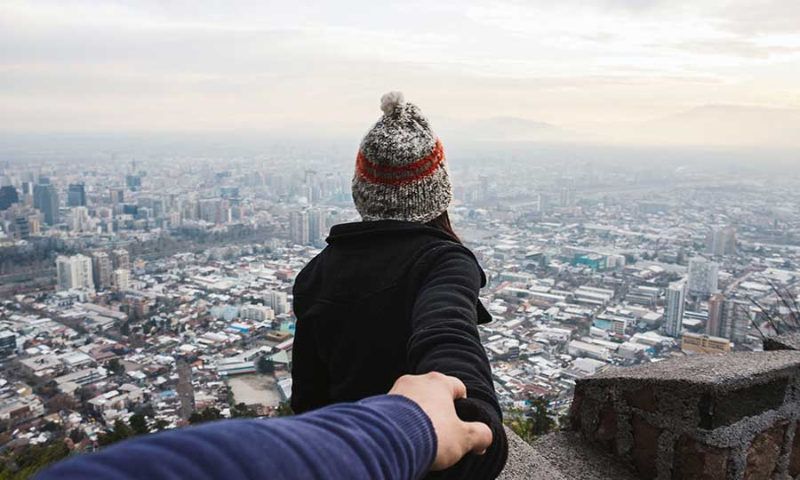 Two people holding hands, looking over the city.